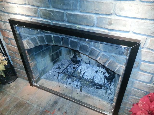 165: We had to fabricate a rectangular frame out of 1-1/4 inch square steel tubing.  We drilled and bolted the frame into the brick. Then we cut and painted aluminum L stock as trim.  All this lets us mount the fireplace doors against the arched opening that otherwise wouldn't accomodate them.