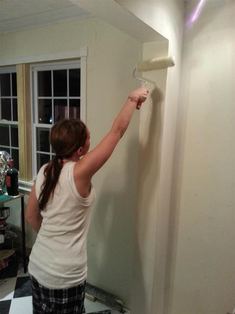 186: Lauren rolls on the very first paint on the stub wall covering the beams post.