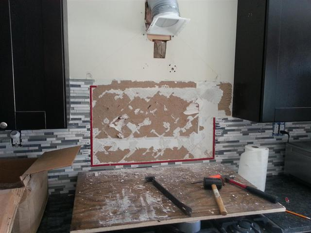 208: Oh, the joys of doing things twice.  Here we are, chipping the first backsplash tile out.  You can see the thinset is pulling chunks of drywall out with it.