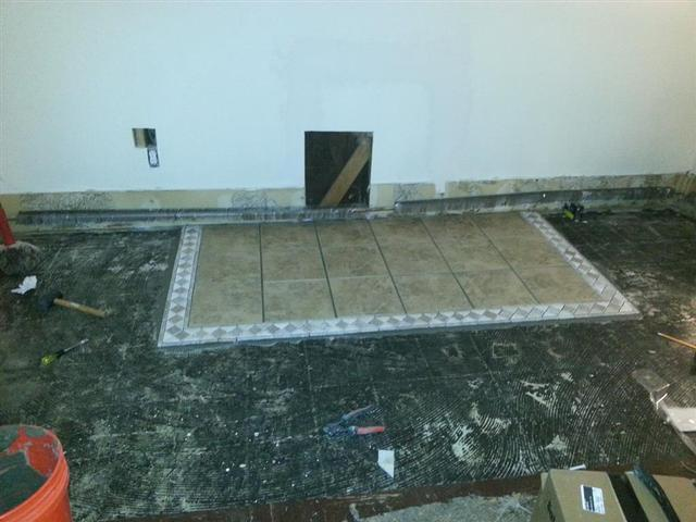 306: The tile for the pellet stove is down, and we cut into the wall to frame out for the vent pipe thimble.